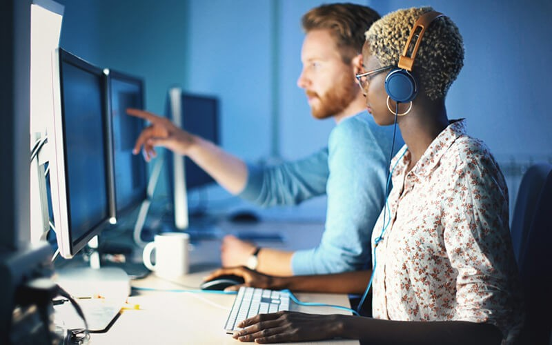 A young man and a young black woman working as a helpdesk representatives